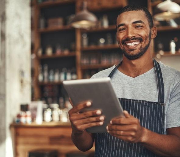 Homem de avental sorri segurando um tablet.