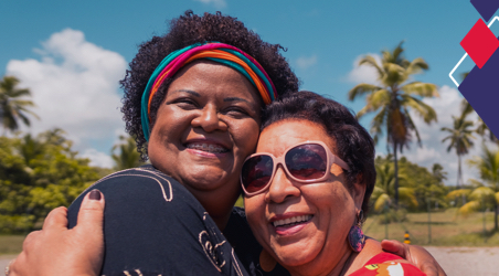 Imagem mostra duas senhoras abraçadas e sorrindo.
