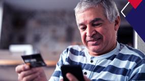 Um senhor segura um cartão de banco com uma mão e olha para o celular na outra mão.