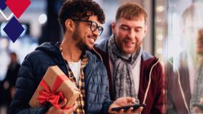 Dois homens andam e conversam sorrindo. O homem da esquerda carrega um presente e o da direita está próximo a uma vitrine.