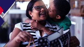 Uma mãe recebe um beijo no rosto do filho.