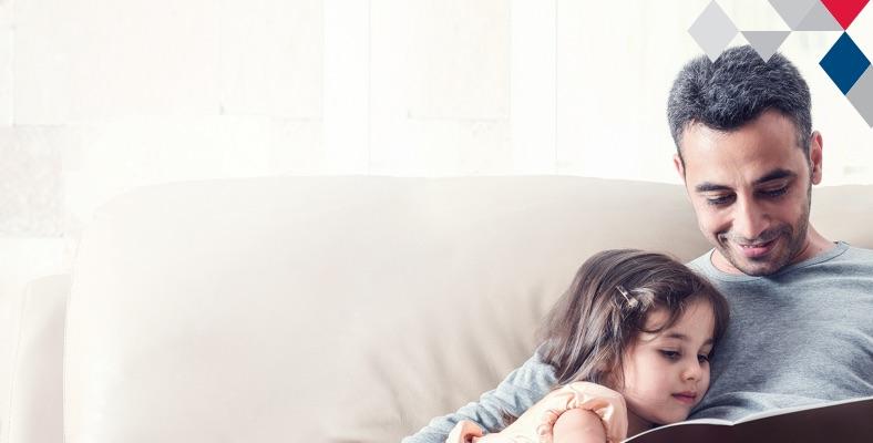 Imagem mostra criança e seu pai sentados no sofá. Ela está olhando para o livro que o pai segura.